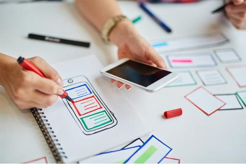 Image of a UX designer sketching while holding a smartphone.