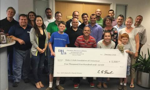 Company's Jeans for Charity group posed with oversized check