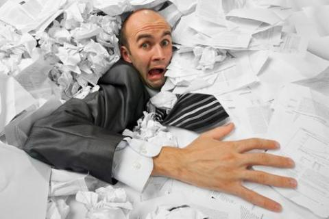 Crazy man buried in paperwork at tax time