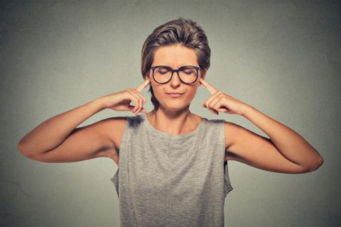 Woman plugging her ears — could be a better boss