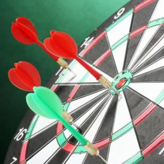 A dartboard with several darts sticking out if it represents a scattershot approach to hiring criteria