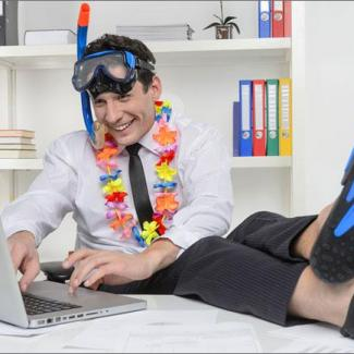 Scuba diver getting ready for a work vacation with laptop and flippers