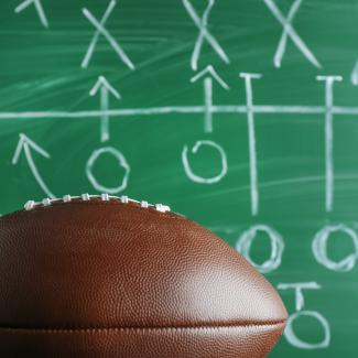 Picture of a football and a chalkboard drawing of a game plan
