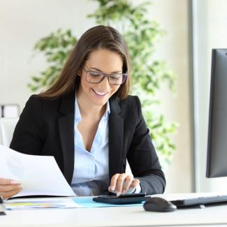 Woman working at office desk preparing to hire a bookkeeper