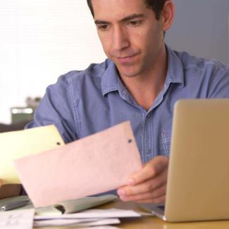 Business owner at laptop who wishes he was hiring an accountant