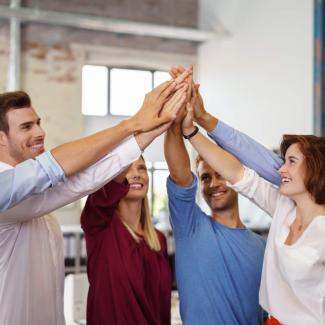 Examples of motivation in the workplace with a group touching hands