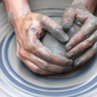 Artist shaping clay on a pottery wheel.
