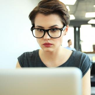 Young woman with glasses looking at a computer screen.