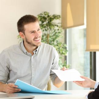 Young male applicant handing his resume to a female hiring manager.