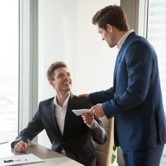 Man in office handing happy man what could be year-end bonus pay.