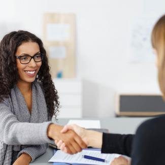 How Managers Can Prepare for a Job Interview — two women shaking hands at an office desk