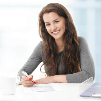 Young, smiling woman holding a pen and in front of a laptop.