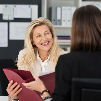 Smiling woman who knows how to make a job offer hands folder to woman