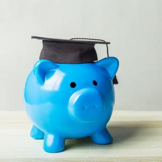 Piggy bank with mortarboard representing salary for recent college graduates