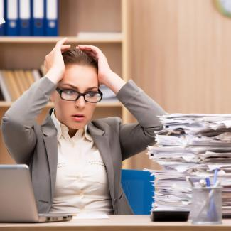 Overworked manager with piles of paper on desk is in need of seasonal employees for help.