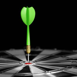 A green dart in the center of the bullseye of a black and white dartboard.
