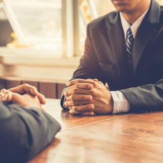 When Should You Start Discussing Salary in an Interview? — two men in suits sitting across from each other at table, hands folded