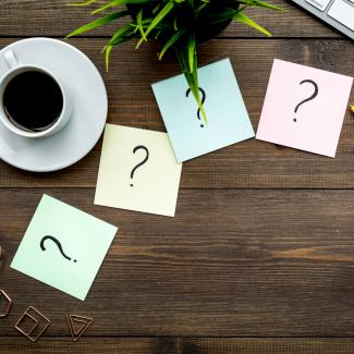 4 Types of Job Interview Questions to Help You Dig Deeper — office table with computer, coffee and question marks on sticky notes