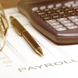 5 Ways to Be More Efficient in Your Payroll Job — calculator, pen and glasses on a spreadsheet with word payroll