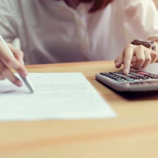 What Payroll Salaries Should You Offer in 2019? — person at desk with calculator