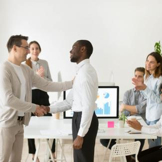 Onboarding Checklist for Temporary Employees — Office team welcomes new worker with clapping and a handshake