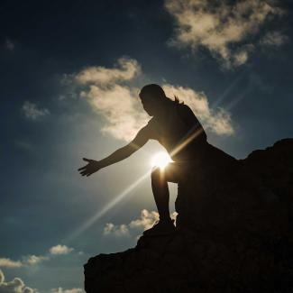 How to Be a Mentor in the Workplace and in Life — woman at top of mountain holding out arm with sun in background