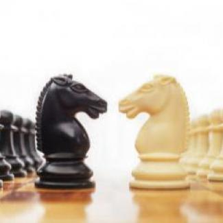 How to Gracefully Resolve Workplace Conflict — depicted with pieces on a chess board