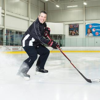 Goal! Keeping Sports Available to Kids — Jim Dinneen holds a hockey stick on ice rink