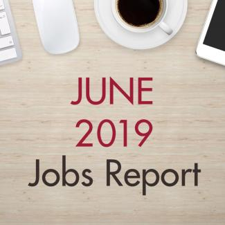 "An image of a desk with text that reads, ""June 2019 Jobs Report"""