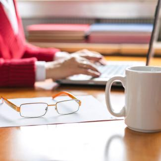 How to Write Payroll Job Descriptions That Attract Top Talent — hands of woman working at laptop next to glasses and coffee cup