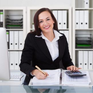 Your Comprehensive Guide to Entry-Level Accounting Jobs — woman working with calculator in front of shelves of notebooks