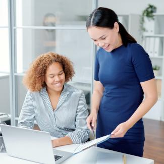 Looking for Temporary Payroll Jobs — Woman standing next to woman at desk looking at paper