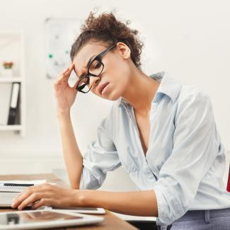 A young woman sitting at a desk in her home office, looking at her laptop with an expression of stress.