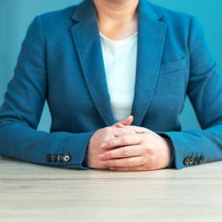 Woman in a blue business suit sitting at table, hands clasped. Her face is not visible.