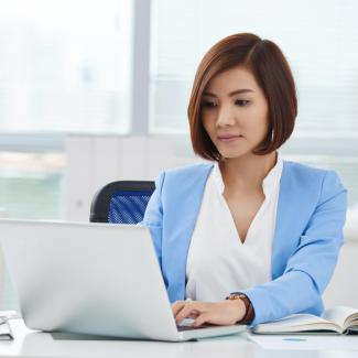 Young woman in a blue jacket working on a laptop in a corporate office.