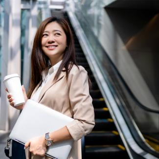 A young, smiling woman at the bottom of an escalator, holding a coffee cup and laptop.