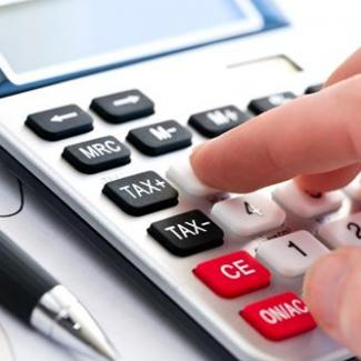 Hand on calculator figuring accounts payable salary