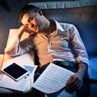 Man sleeping at his desk at night