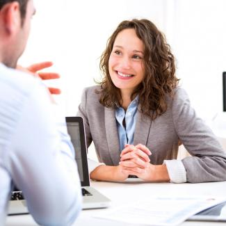 25 of the Best Interview Questions for Administrative Assistants — A smiling job candidate interviews with a hiring manager