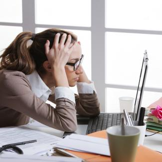 4 Ways to Prevent Work Burnout at Your Company — a woman holds her head in front of her computer at work