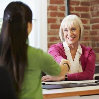 A hiring manager shakes hands with an administrative job candidate and prepares to ask her interview questions