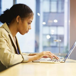 6 New Year Goals for the Job Seeker — a woman looks for employment opportunities on her laptop