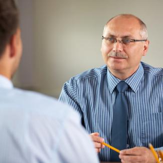 A hiring manager interviews a job candidate as he attempts to staff open jobs