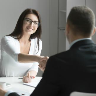 Two people shaking hands in a job interview.
